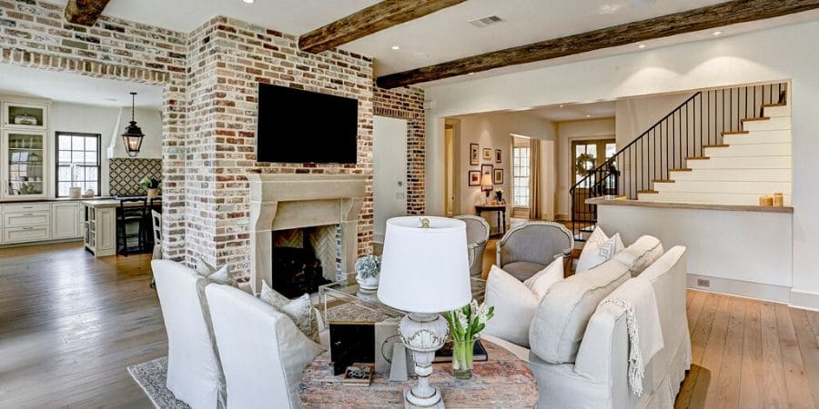 Transitional style living room with fireplace and exposed wood beams, remodeled by Southern Green Builders in Houston, Texas